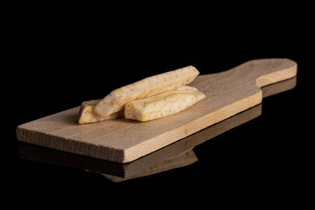 Group of three whole dry vegetable chip of taro on small wooden cutting board isolated on black glass