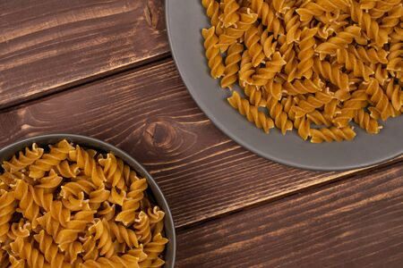 Lot of whole dry brown wholegrain fusilli on gray ceramic plate in gray ceramic bowl flatlay on brown wood Stok Fotoğraf