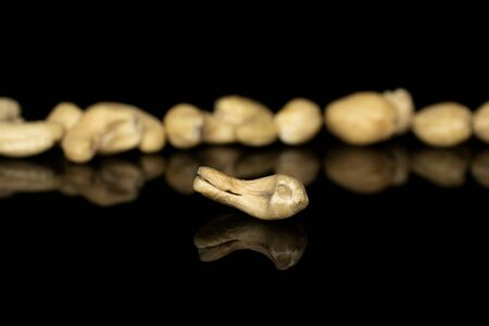 Lot of whole brown nut cashew isolated on black glass