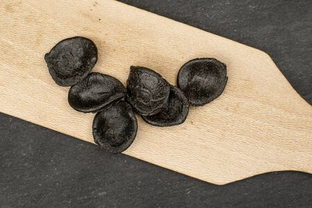 Group of seven whole colorful pasta orecchiette on wooden cutting board flatlay on grey stone