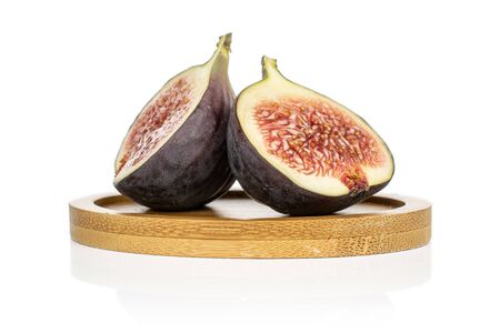 Group of two halves of sweet purple fig on round bamboo coaster isolated on white background