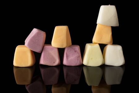 Group of nine whole soft pastel candy isolated on black glass