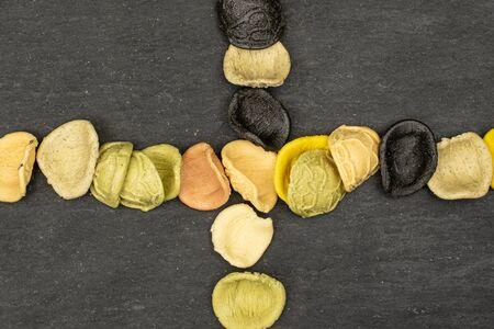 Lot of whole colorful pasta orecchiette crossed flatlay on grey stone