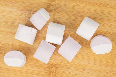 Group of eight whole sweet pastel marshmallow flatlay on light wood
