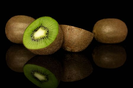 Group of two whole two halves of exotic brown kiwi isolated on black glass Reklamní fotografie