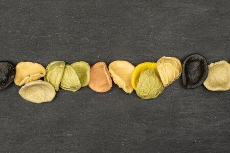 Lot of whole colorful pasta orecchiette flatlay on grey stone