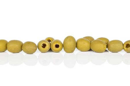 Lot of whole marinated green olive in row isolated on white background