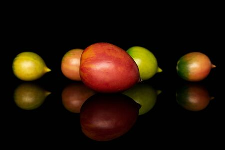 Group of five whole fresh tomato de barao isolated on black glass