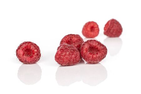 Group of six whole fresh red raspberry isolated on white background