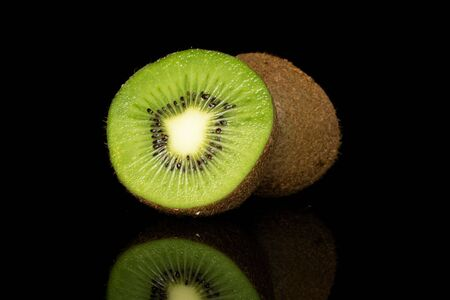 Group of two halves of exotic brown kiwi isolated on black glass Reklamní fotografie