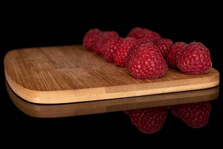 Lot of whole fresh red raspberry on bamboo cutting board isolated on black glass Stok Fotoğraf