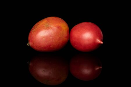 Group of two whole fresh tomato de barao isolated on black glass