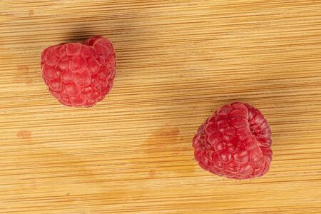 Group of two whole fresh red raspberry flatlay on light wood