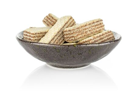 Lot of whole crispy beige hazelnut wafer cookie in dark ceramic bowl isolated on white background