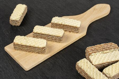 Lot of whole crispy beige hazelnut wafer cookie on small wooden cutting board on grey stone