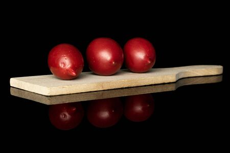 Group of three whole fresh tomato de barao on wooden cutting board isolated on black glass