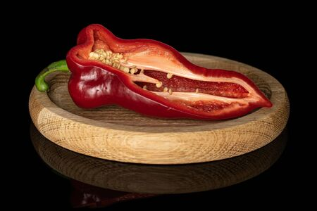 One half of sweet red bell pepper on bamboo plate isolated on black glass Stock Photo
