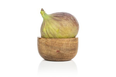 One whole sweet purple fig in bamboo bowl isolated on white background