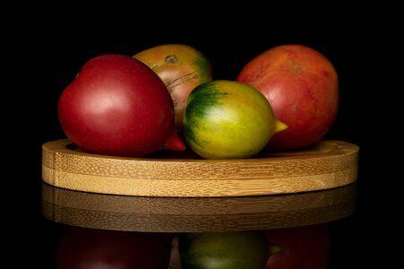 Group of four whole fresh tomato de barao on round bamboo coaster isolated on black glass
