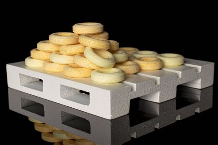 Lot of whole round pale yellow candy on white pallet isolated on black glass Stok Fotoğraf