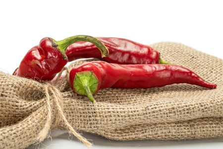 Group of three whole dark red fresh hot pepper with jute bag isolated on white background Stock Photo