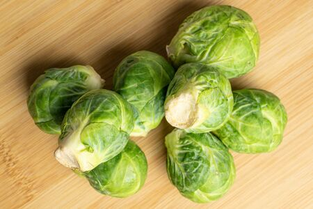 Group of eight whole fresh green brussels sprout flatlay on light wood 版權商用圖片