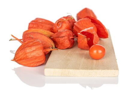 Lot of whole fresh orange physalis on wooden cutting board isolated on white background Zdjęcie Seryjne