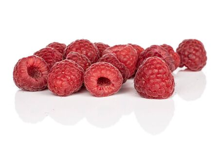 Lot of whole disordered fresh red raspberry isolated on white background
