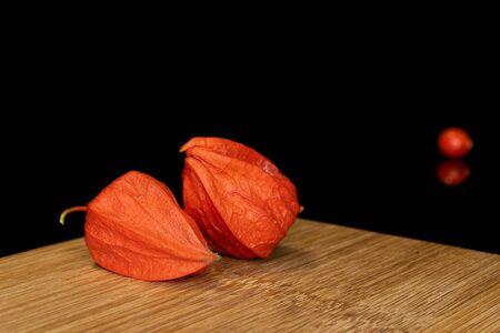 Group of three whole fresh orange physalis on bamboo cutting board isolated on black glass Zdjęcie Seryjne