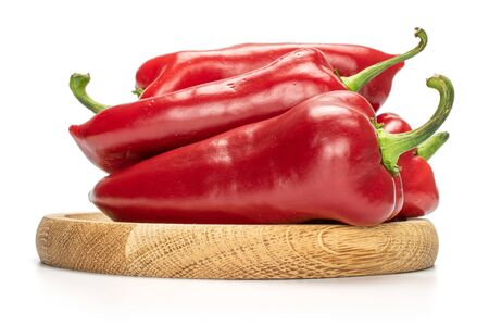 Group of four whole sweet red bell pepper on bamboo plate isolated on white background
