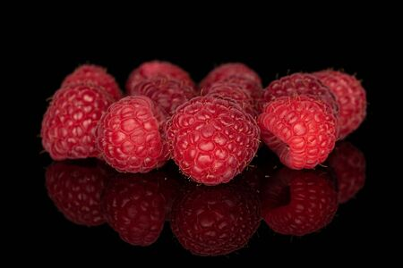 Lot of whole fresh red raspberry isolated on black glass