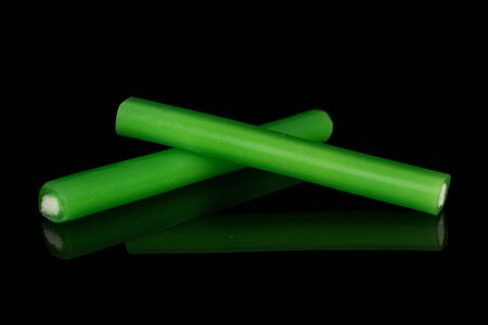 Group of two whole sweet stick candy isolated on black glass