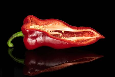 One half of sweet red bell pepper isolated on black glass
