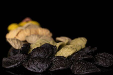 Lot of whole colored colorful pasta orecchiette isolated on black glass Banco de Imagens