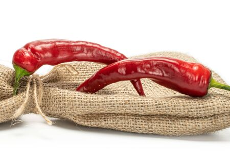 Group of two whole red fresh hot pepper with jute bag isolated on white background