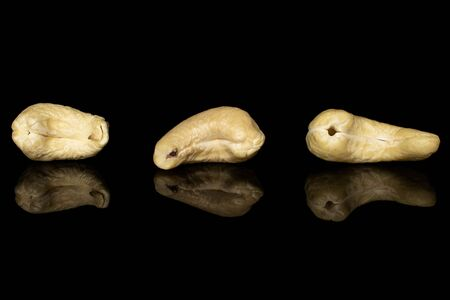 Group of three whole brown nut cashew isolated on black glass