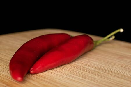 Group of two whole hot red chili cayenne on bamboo cutting board isolated on black glass Stock Photo