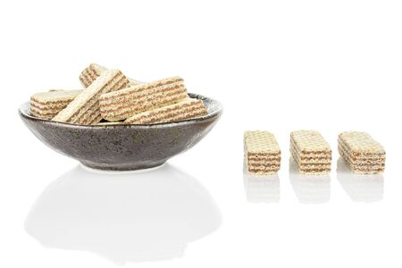 Lot of whole crispy beige hazelnut wafer cookie in dark ceramic bowl isolated on white background 写真素材 - 131951942