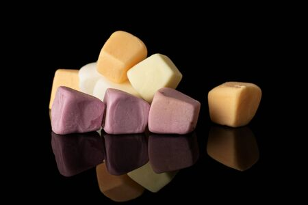 Lot of whole soft pastel candy isolated on black glass 스톡 콘텐츠