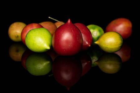Group of ten whole fresh tomato de barao isolated on black glass Stock Photo