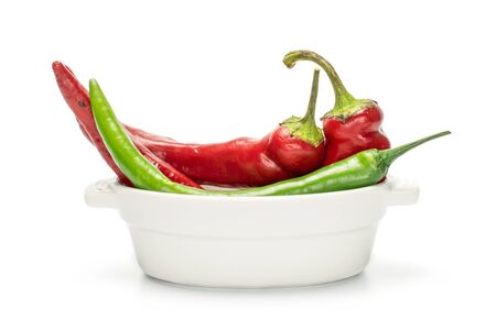Group of three whole fresh hot pepper in ceramic stewpan isolated on white background Stock Photo