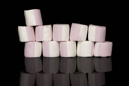 Lot of whole sweet pastel marshmallow wall isolated on black glass Imagens