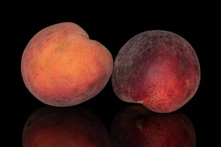 Group of two whole sweet red peach isolated on black glass