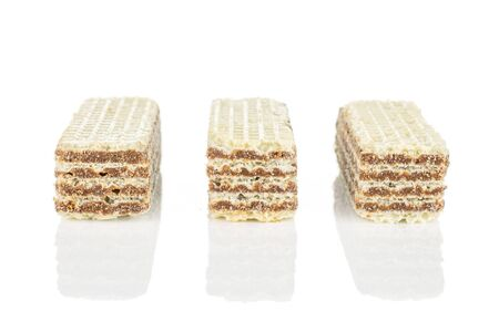 Group of three whole crispy beige hazelnut wafer cookie in row isolated on white background
