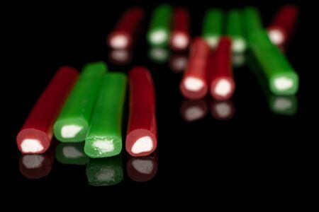 Group of thirteen whole sweet stick candy isolated on black glass