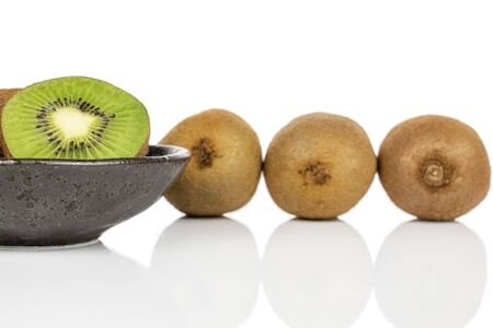 Group of three whole one half of exotic brown kiwi on glazed bowl isolated on white background 写真素材