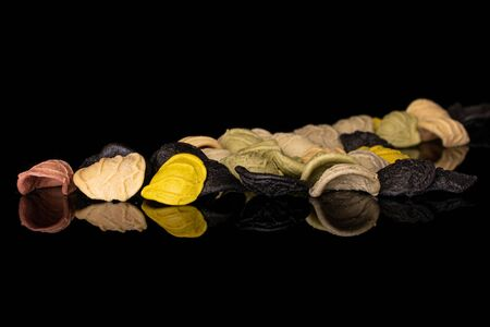 Lot of whole colored colorful pasta orecchiette isolated on black glass Reklamní fotografie