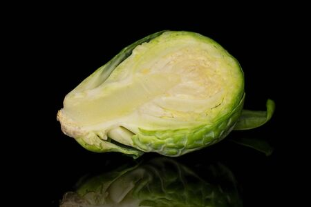 One half of fresh green brussels sprout isolated on black glass