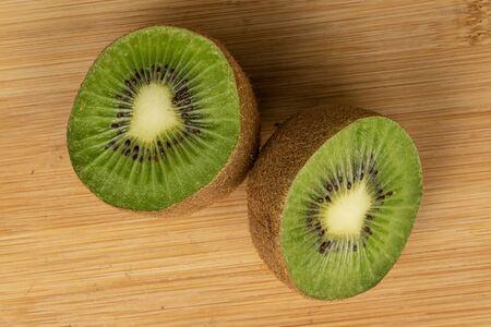 Group of two halves of exotic brown kiwi flatlay on light wood Reklamní fotografie