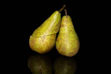 Group of one whole two halves of fresh green pear conference isolated on black glass